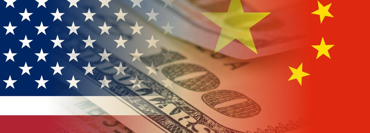 US and China flags with banknotes.