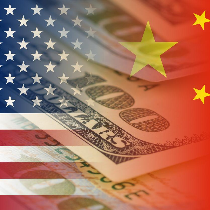 US and China flags with banknotes